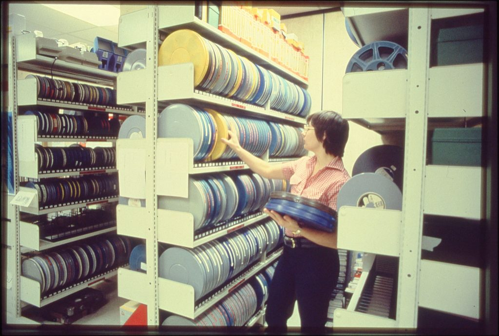Elaine Lang shelving 16mm film reels 1970s